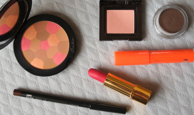 Clockwise from the far left: Guerlain Crazy Terracotta Healthy Glow Powder; Laura Mercier eyeshadow single in Crystal Beige; Clarins eyeshadow pot in Earth; Bourjois Colour Boost Lip Crayon in Orange Punch; Chanel Rouge Allure Velvet in L'Exuberante; MAC eyeliner pencil in Teddy.